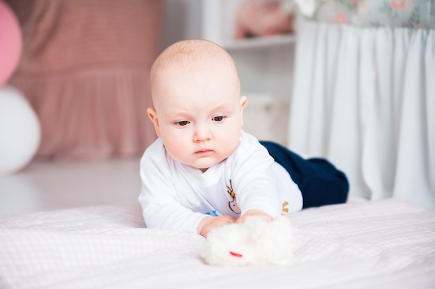 Foto van schattige babyjongen tot op de vloer in haar kinderkamer en spelen met speelgoed