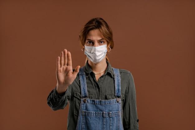 Foto van schattige boerin met gezichtsmasker toont lockdown en quarantainetijd. draagt denim overall, geïsoleerde bruine kleur achtergrond.