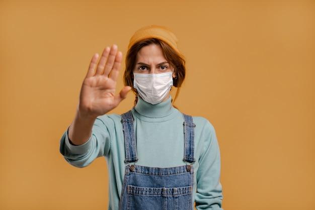 Foto van schattige boerin met gezichtsmasker voor quarantainetijdshow om afstand te houden. draagt denim overall en hoed, geïsoleerde bruine kleur achtergrond.
