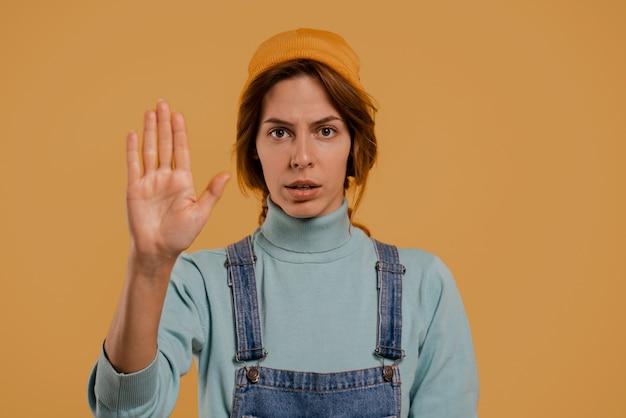 Foto van schattige boerin voor quarantainetijdshow om afstand te houden. draagt denim overall en hoed, geïsoleerde bruine kleur achtergrond.