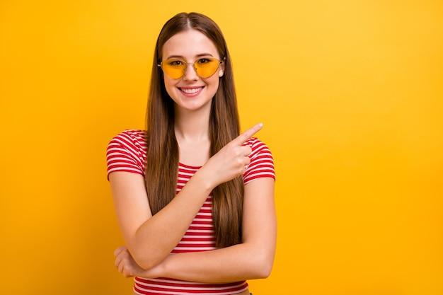 Foto van schattige charmante jonge promotor meisje gevouwen armen glimlachend wijzende vinger lege ruimte voorstelt fijne korting slijtage zon specs gestreept wit rood shirt levendige gele kleur achtergrond