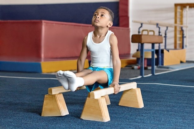 Foto van schattige donkere huid kleine gymnast die op parallelle staven concurreert.