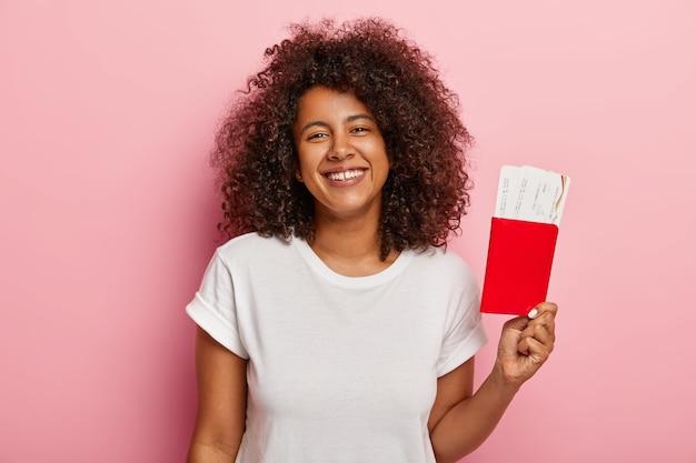 Foto van schattige donkere vrouw houdt kaartjes en paspoort, verheugt zich op zomervakantie en reis, blij dat haar droom eindelijk uitkwam, gekleed in een wit t-shirt, wacht op het vliegtuig. reizend concept