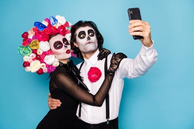 Foto van schattige grappige zombie paar man dame meisje omhelzing vasthouden telefoon maken selfie vertalen festival dragen zwarte jurk dood kostuum rozen hoofdband bretels geïsoleerde blauwe kleur achtergrond Premium Foto