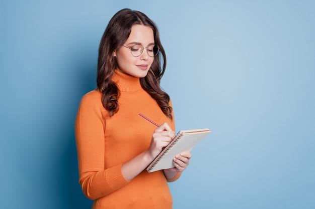Foto van schattige intelligente schrijver vrouw schrijft notities in kladblok op blauwe achtergrond