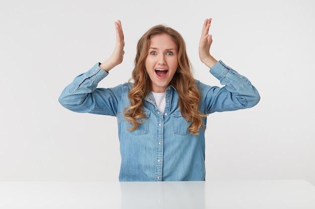 Foto van schattige jonge blonde vrouw heft zijn handen op en schreeuwt in shock, geïsoleerd op witte achtergrond. mensen en emotie concept.