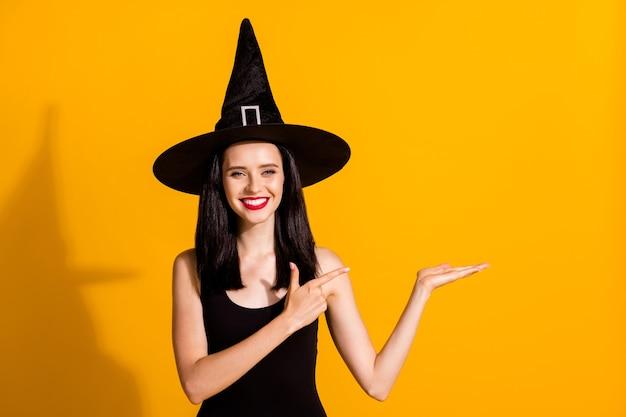 Foto van schattige mooie jonge goochelaar dame brede glimlach houd lege ruimte richting vinger perfecte aanbeveling dragen zwarte tovenaar hoofddeksel jurk geïsoleerde felgele kleur achtergrond