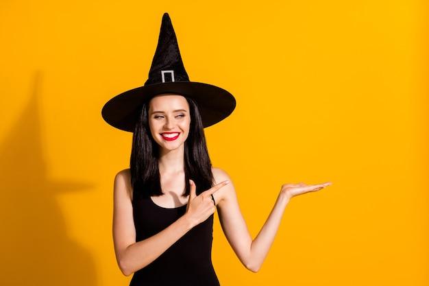 Foto van schattige mooie jonge goochelaar dame open palm kijken lege ruimte regisseren vinger presenteren nieuw product dragen zwarte tovenaar hoofddeksels jurk geïsoleerde felgele kleur achtergrond