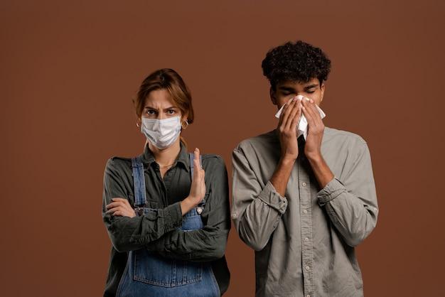 Foto van schattige paar boeren, vrouw met gezichtsmasker toont afstand terwijl man zijn neus snuit. draagt denim overall, geïsoleerde bruine kleur achtergrond.
