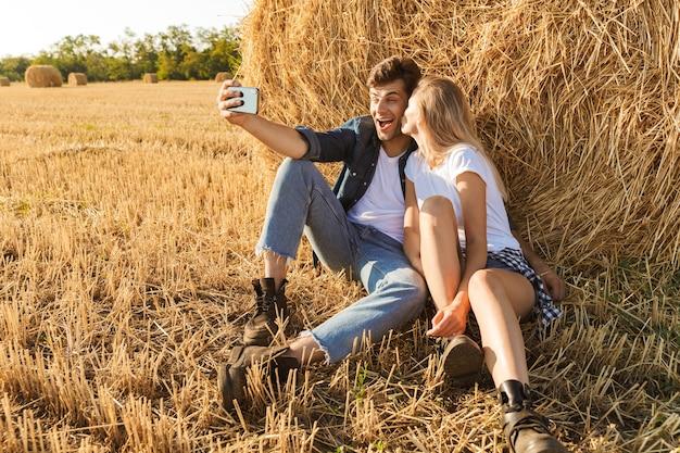 Foto van schattige paar man en vrouw selfie te nemen zittend onder grote hooiberg in gouden veld, tijdens zonnige dag