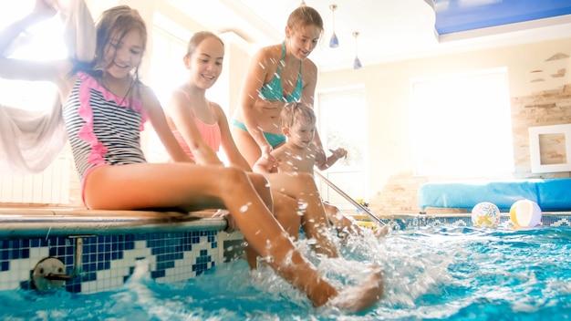 Foto van schattige peuterjongen met jonge moeder en oudere zus die bij het zwembad zitten en water opspatten. familie spelen en plezier maken bij het zwembad