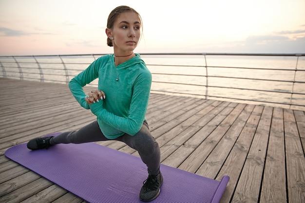 Foto van schattige slanke sportieve jonge vrouw in yoga pose, sportkleding gekleed, treinen aan zee, maakt ochtend uitrekken.