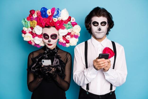 Foto van schattige spookachtige twee mensen man dame houdt telefoons lees nieuws ondode heilige rennen voor president dragen zwarte jurk dood kostuum rozen hoofdband bretels geïsoleerde blauwe kleur achtergrond