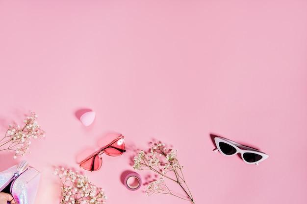 Foto van schattige twee zonnebril op roze muur met bloemen
