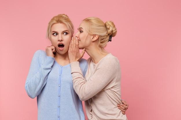 Foto van schattige tweelingen blondines, het meisje vertelt haar zus het ongelooflijke nieuws over, de tweede opende verrast haar mond, staat op een roze achtergrond.
