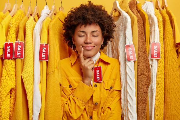 Foto van schattige vrouw met afro-kapsel, probeert nieuwe gele jas in kleedwinkel, houdt de ogen gesloten, staat tussen kleding met rode labels met inscriptie uitverkoop, zoekt naar modieuze outfit.