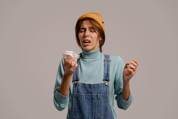 Foto van schattige vrouwelijke hipster niest en ziet eruit alsof ze ziek is geworden. blanke vrouw draagt denim overall en hoed geïsoleerde grijze kleur achtergrond.