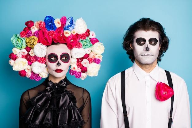 Foto van schattige zombie demon paar man dame serieuze blik ogen doen alsof cool hebben diepe wederzijdse genegenheid dragen zwarte jurk dood kostuum rozen hoofdband bretels geïsoleerde blauwe kleur achtergrond