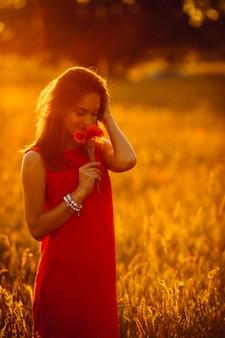 Foto van schitterende dame in rode kleding die zich op gouden de zomergebied bevindt