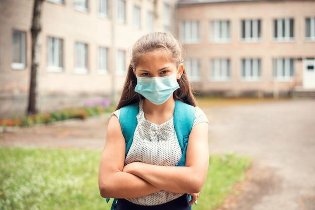 Foto van schoolmeisje student klaar om naar school te gaan, ze haat epidemische regels, medische masker irriteert haar