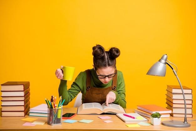 Foto van schoolmeisje zit bureau houdt koffiekopje lees leerboek op gele achtergrond