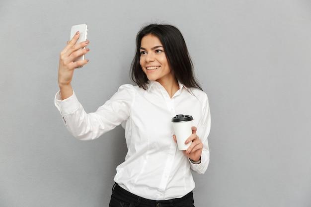 Foto van secretaresse vrouw in formele slijtage staande afhaalmaaltijden koffie in de hand te houden en selfie te nemen op mobiele telefoon, geïsoleerd op grijze achtergrond