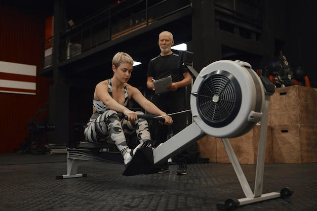 Foto van senior bebaarde mannelijke fitness insturctor met klembord kijken naar zijn vrouwelijke cliënt oefenen op roeimachine. aantrekkelijke vrouw training in de sportschool met persoonlijke coach, cardiotraining