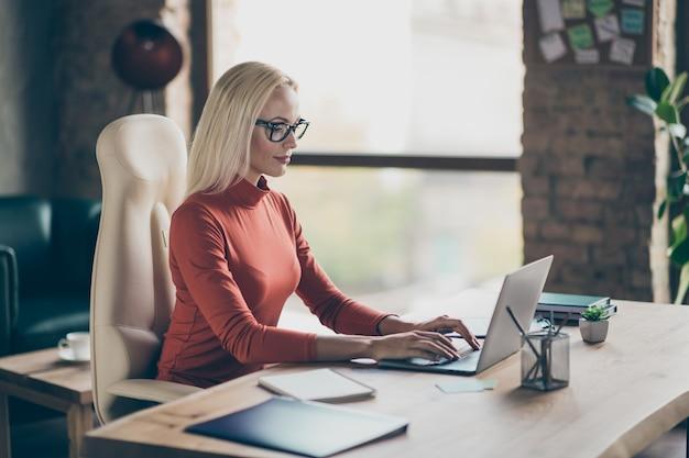 Foto van serieus geïnteresseerde, doordachte vrouw die op laptop door sociale media bladert op zoek naar geschikte gegevens die als contentmanager werken
