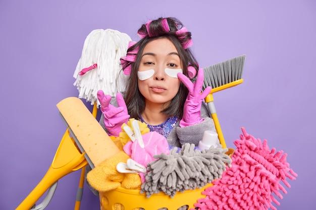 Foto van serieuze jonge aziatische vrouw die patches onder de ogen aanbrengt, heeft een nauwgezette blik die geeft om reinheid en zuiverheid, druk bezig met huishoudelijk werk geïsoleerd over paarse muur