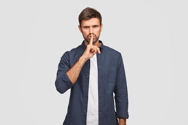 Foto van serieuze man houdt wijsvinger op lippen zoals stil gebaar demonstreert