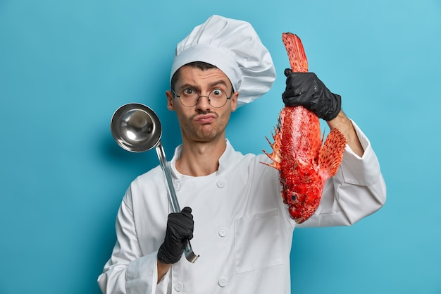 Foto van serieuze professionele chef-kok houdt pollepel en vis, bereidt gastronomische zeevruchtenschotel, draagt witte uniform, zwarte handschoenen, kookt soep van rode bas