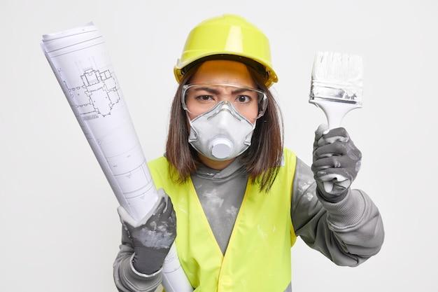 Foto van serieuze, strikte vrouwelijke bouwer die op de bouwplaats werkt, bereidt architecturale planningen voor, houdt de bouwblauwdruk vast en de kwast draagt een beschermend uniform