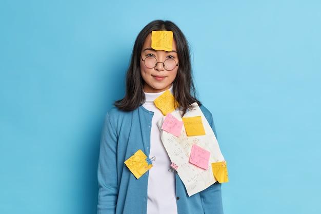 Foto van serieuze student maakt aantekeningen op stickers en papieren om te onthouden informatie draagt ronde bril bereidt zich voor op privéles werkt over cursussen op de universiteit.