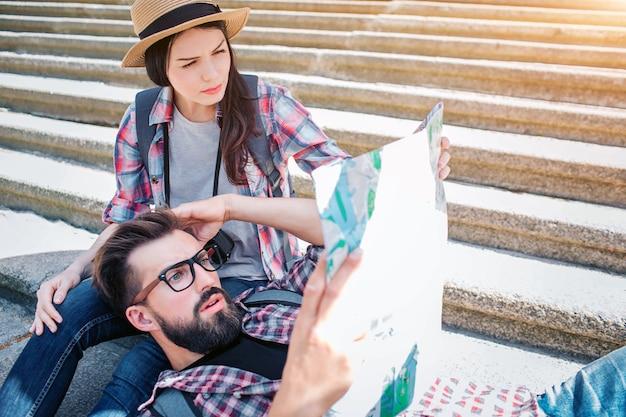 Foto van serieuze toeristen op stappen. hij ligt op de knieën van het vriendin en houdt de kaart in hanad. ze zit op trappen. ze zijn verward en geconcentreerd.