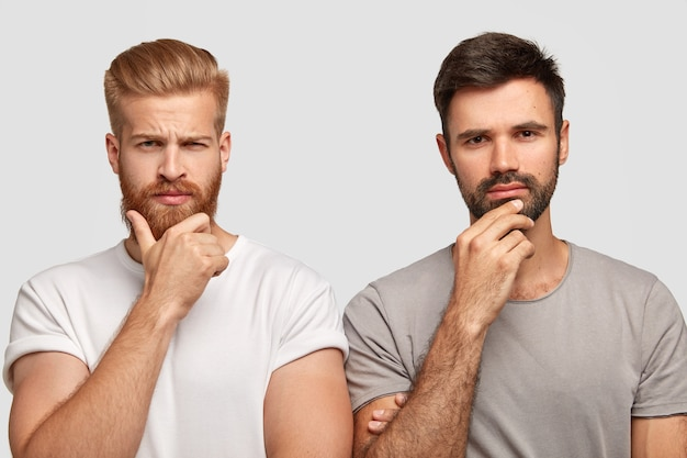 Foto van serieuze twee mannen houden kin vast, gekleed in casual t-shirts, model tegen een witte muur, diep in gedachten verzonken, een uitweg vinden uit het probleem. gember man en zijn vriend poseren binnen bij