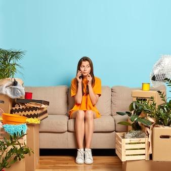 Foto van serieuze vrouw belt iemand via smartphone, zit op een comfortabele bank, deelt nieuws over het kopen van een nieuw appartement, omringd met persoonlijke bezittingen, ontspant in een nieuw huis. bewegend concept