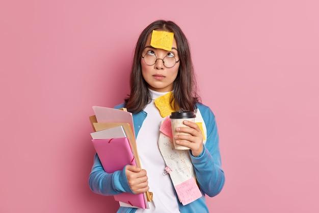 Foto van serieuze vrouwelijke student heeft koffiepauze hierboven geconcentreerd heeft herinnerende sticker op voorhoofd geplakt