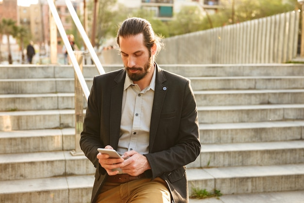 Foto van serieuze zakelijke man 30s in formeel pak met behulp van mobiele telefoon, tijdens een wandeling door de stad en staande op trappen in stedelijk gebied
