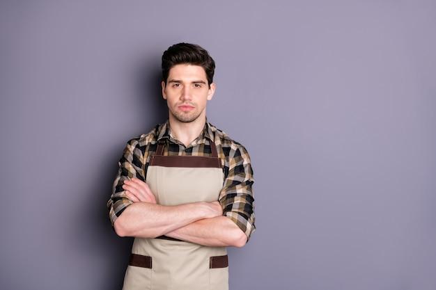 Foto van serieuze zelfverzekerde barista met gekruiste armen peinzend naar je kijken in de buurt van lege ruimte geïsoleerde grijze kleur muur