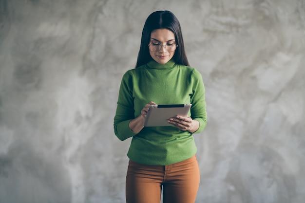 Foto van seriouc geconcentreerde gefocuste vrouw die door gevonden informatie op haar tablet in bril kijkt geïsoleerde grijze muur kleur concrete achtergrond
