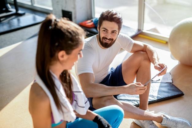 Foto van sexy sterke persoonlijke fitnesstrainer en zijn cliënt zitten in de sportschool en praten.