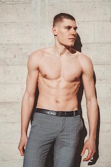 Foto van shirtless knappe man voor een muur buiten