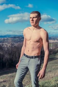 Foto van shirtless man poseren buiten