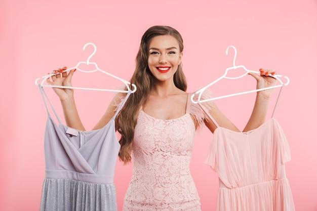 Foto van shopaholic vrouw 20s houden en kiezen van twee jurken op hangers tijdens het winkelen, geïsoleerd over roze muur