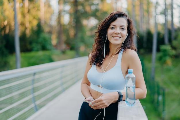 Foto van slanke mooie gekrulde vrouw gekleed in bijgesneden top en legging geniet van luisteren muziek houdt mobiele telefoon drinkt vers water uit fles poses bij bridge poses tegen natuur achtergrond