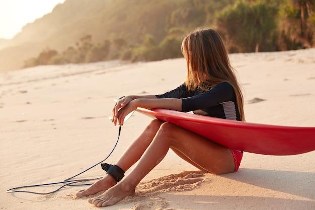 Foto van slanke surfer-beginner in zwembroek, neemt pauze na het oefenen van surfen op grote oceaangolven
