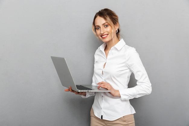 Foto van slimme vrouw in formele slijtage staande en met laptop op kantoor, geïsoleerd