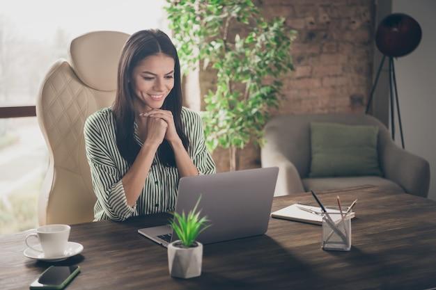 Foto van slimme zakelijke dame kijkt naar het netbook-scherm op moderne loft