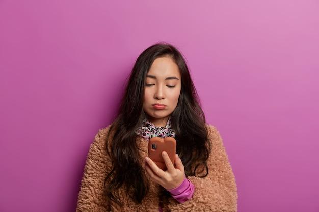 Foto van sombere brunette vrouw kijkt naar scherm van mobiele telefoon met droevig gezicht, leest slecht nieuws, voelt ontevredenheid na ontvangst van bericht