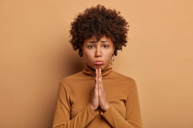 Foto van sombere donkere gekrulde vrouw vraagt om het beste, houdt de handpalmen tegen elkaar gedrukt, vraagt om vergeving, nonchalant gekleed, geïsoleerd over bruine muur, doet een verzoek. doe me alsjeblieft een plezier